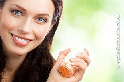 Bild einer Frau, die Nahrungsergänzungsmittel in der Hand hält